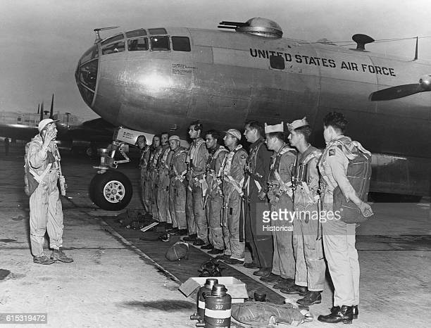 The crew of a B-29 listens to a briefing before a raid on North Korea on an airfield in Japan beside the nose of their bomber.