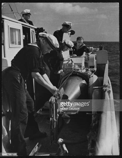The crew of a German gunboat prepare a torpedo