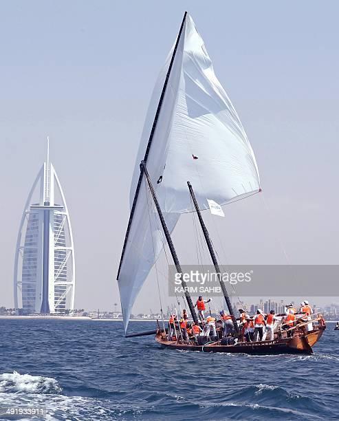 The crew of AlBarraq a dhow skippered by Musabeh Rashid alFattan alFalasi sails towards the finishing line near Dubai's landmark Burj AlArab hotel to...