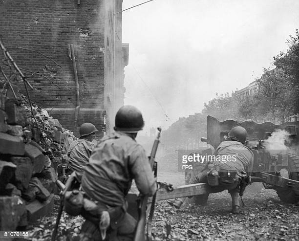 The crew of an American 57mm antitank gun fire on a German defensive position in the tower seen in the background Aachen Germany 15th October 1944