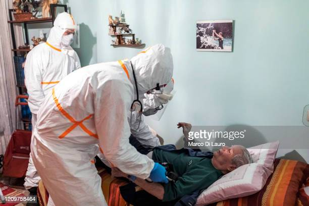 The crew of an Italian Red Cross ambulance assists a man showing symptoms of COVID19 during an emergency intervention on April 4 2020 in Bergamo...