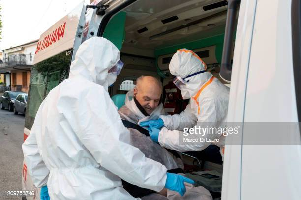The crew of an Italian Red Cross ambulance assists a suspected COVID19 patient during an emergency intervention on April 8 2020 in Bergamo Italy The...