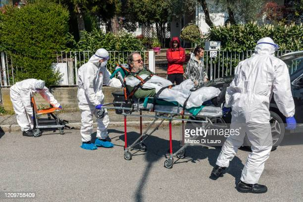 The crew of an Italian Red Cross ambulance assists a suspected COVID19 positive patient during an emergency intervention on April 4 2020 in Bergamo...