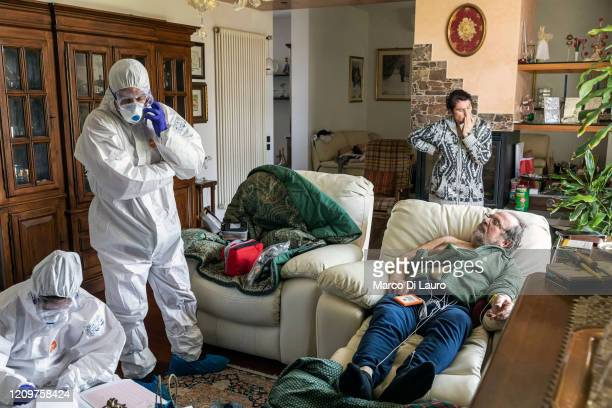 The crew of an Italian Red Cross ambulance assists a suspected COVID-19 positive patient during an emergency intervention on April 5, 2020 in...