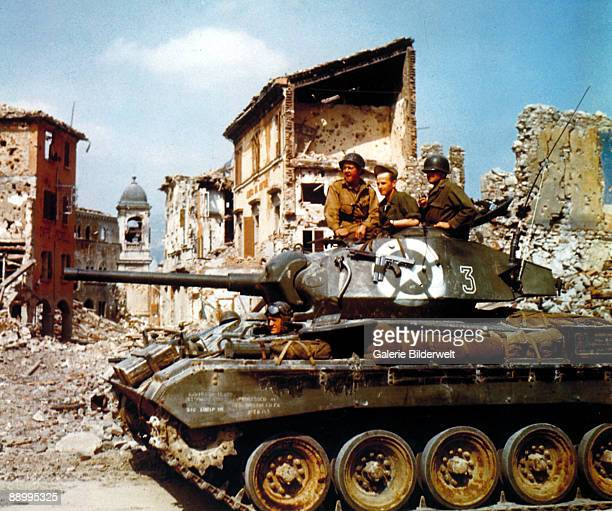 The crew of an M24 Chaffee light tank of the US 81st Cavalry Reconnaissance Squadron, 1st Armored Division, driving along a war-ravaged street near...