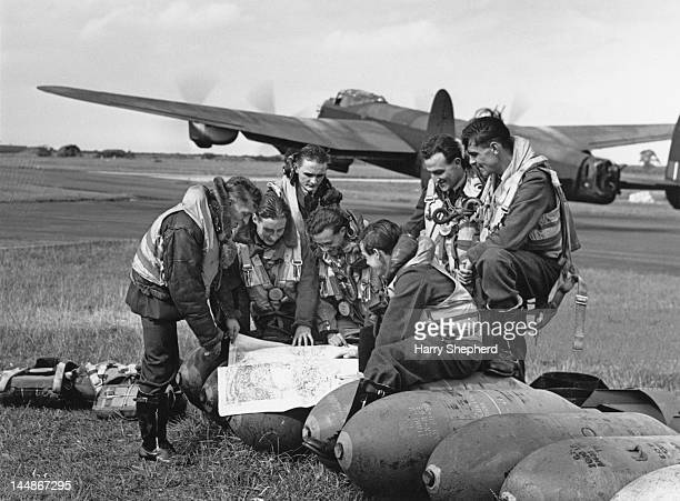 The crew of an RAF Lancaster bomber discuss their flight before takeoff from an airfield in East Anglia 15th September 1944 They are preparing to...