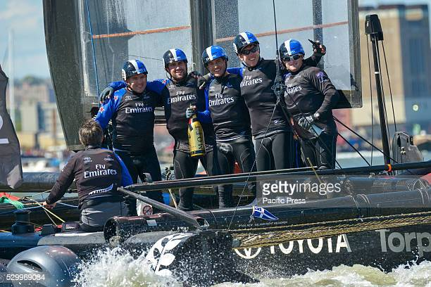 The crew of Emirates Team New Zealand poses with a celebratory bottle of champagne after winning the third race Six competitors for the Louis Vuitton...