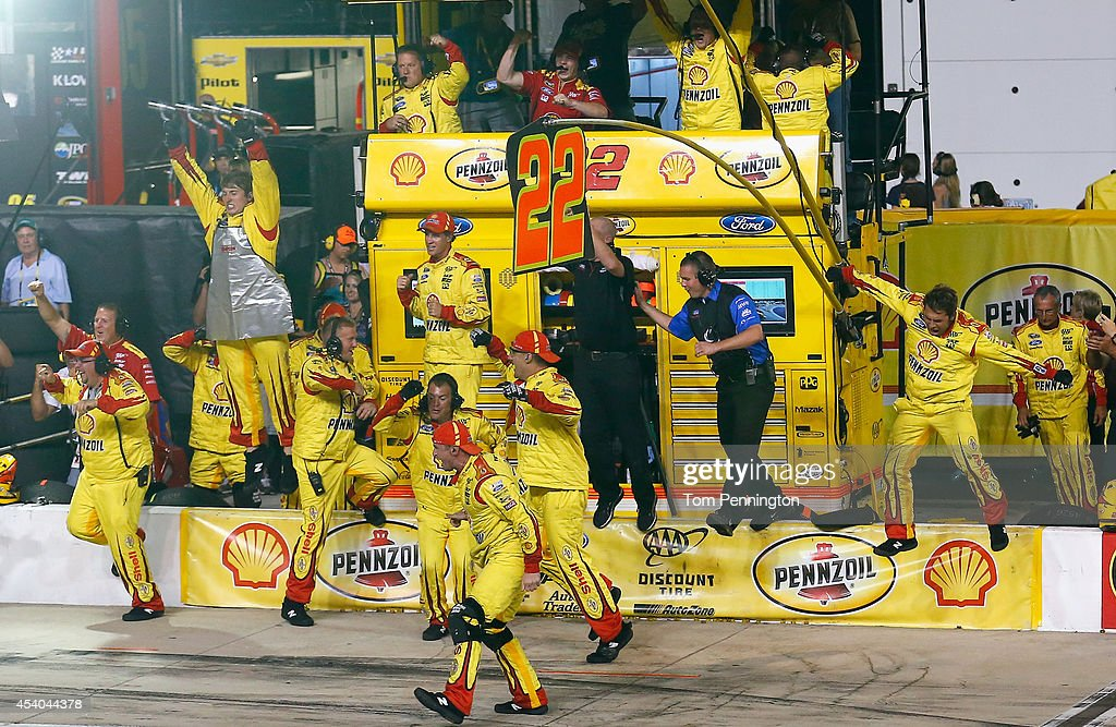 The crew of Joey Logano, driver of the #22 Shell Pennzoil Ford, reacts after winning the NASCAR Sprint Cup Series Irwin Tools Night Race at Bristol Motor Speedway on August 23, 2014 in Bristol, Tennessee.
