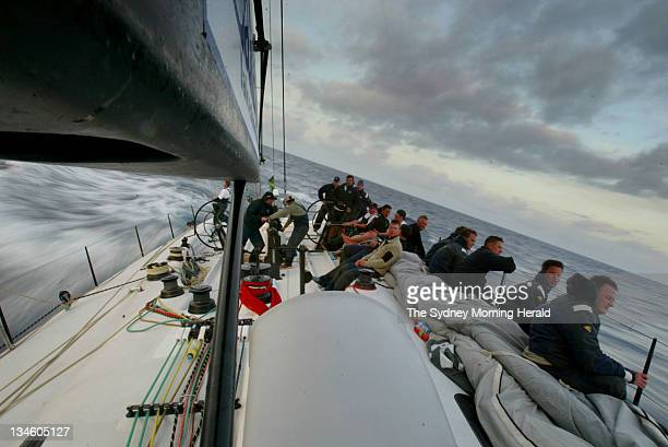 The crew of Konica Minolta is rugged up in wet weather gear and on the rail as it prepares for nightfall off the NSW South Coast during the 2005...