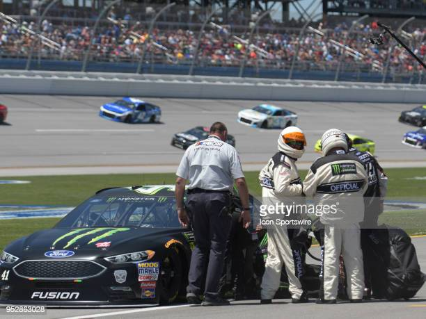 The crew of Kurt Busch StewartHaas Racing Ford Fusion Monster Energy / Haas Automation and NASCAR Officials work to replace a broken radio before the...