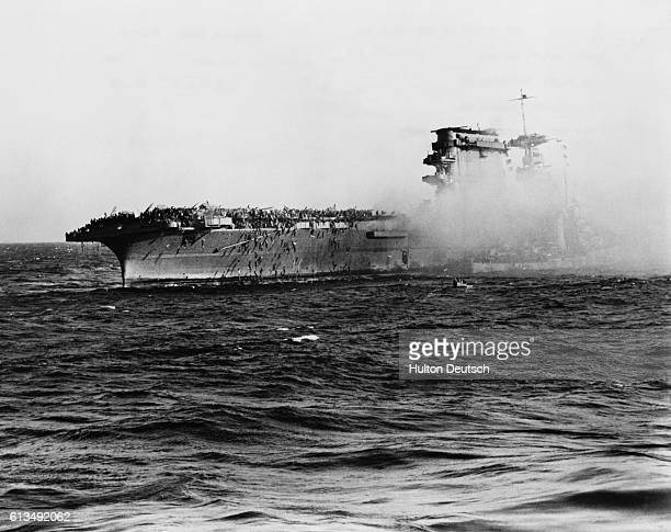 The crew of the aircraft carrier USS Lexington abandons ship as ordered by their captain during the Battle of the Coral Sea A destroyer obscured by...