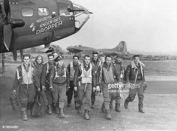 The crew of the B17 Flying Fortress Knockout Dropper bomber walk away from their plane At center wearing a flak jacket is pilot John P Manning To the...