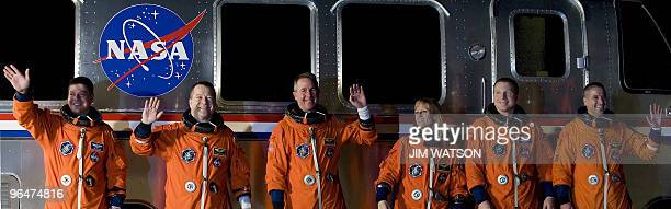 The crew of the space shuttle Endeavour STS130 wave as they pose in front of the astrovan at Kennedy Space Center in Florida on February 7 2010 in...