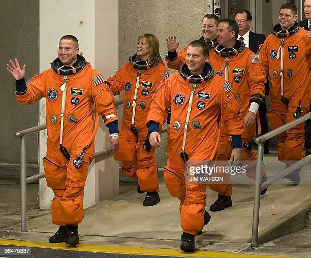 The crew of the space shuttle Endeavour STS130 wave as they walk out to the astrovan at Kennedy Space Center in Florida on February 7 2010 in advance...
