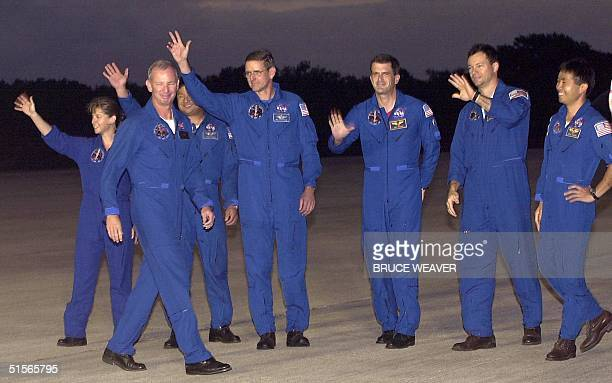 The crew of the US space shuttle Discovery wave to the media as they arrive 01 October at Kennedy Space Center The crew are US Pilot Pam Melroy US...