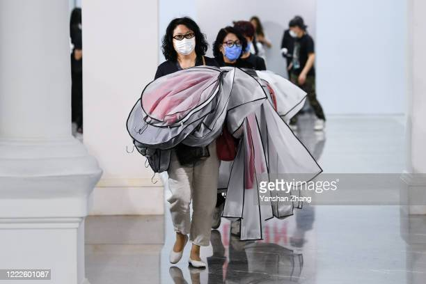 The crew wear face masks as a preventive measure against the COVID-19 coronavirus as they leave following the DEJIN collection show by Chinese...