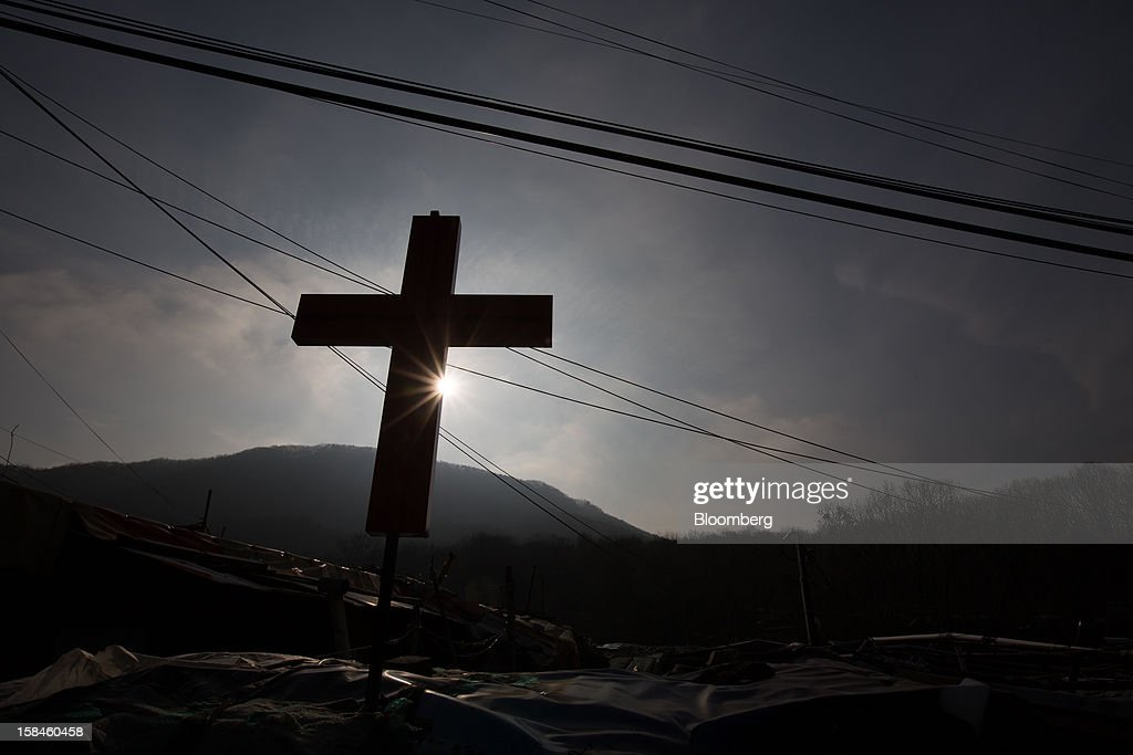 The cross of a church is silhouetted against the sun in Guryong village in the Gangnam district of Seoul, South Korea, on Sunday, Dec. 16, 2012. South Koreans vote on Dec. 19 to replace President Lee Myung Bak, whose five-year term ends in February. Photographer: SeongJoon Cho/Bloomberg via Getty Images
