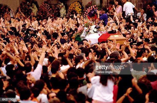 The crowd applaud at the passage of the coffins of Italian judge Paolo Borsellino and his police escort during their funerals at the Palermo...