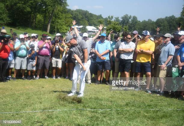 The crowd at the green looks on as Rory McIlroy hits a shot from beyond the ropes back on to the green during the third round of the PGA Championship...