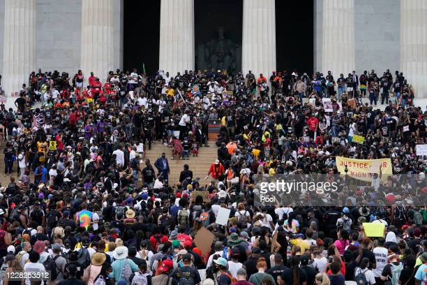 The crowd begins to surround Rev. Al Sharpton, at center, as he introduces families of people who have been killed by police, during the March on...