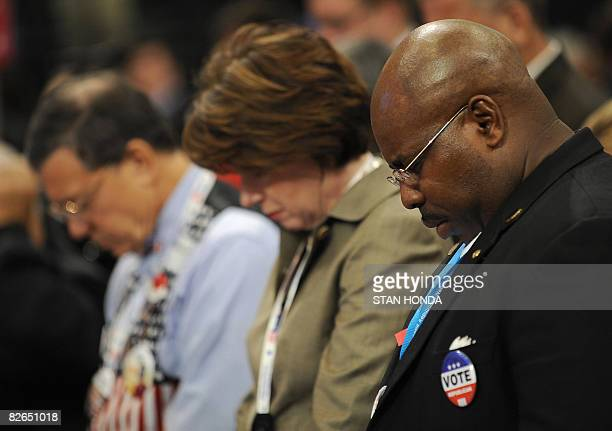 The crowd bows in prayer during an invocation by Father Edward Reese at the US Republican National Convention at the Xcel Energy Center in St Paul...