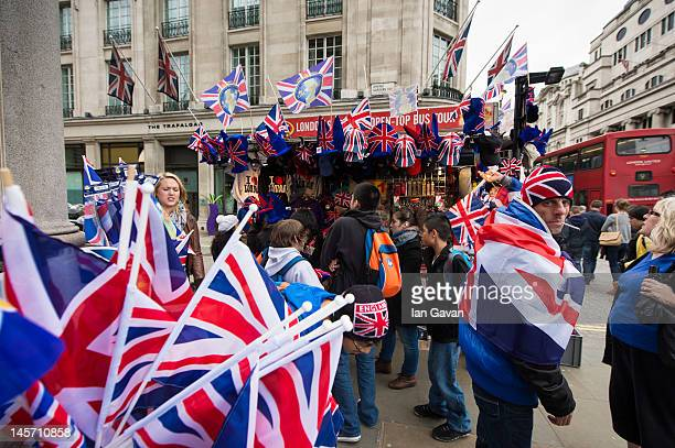 The crowd buy flags and hats from a street vendor prior to the Diamond Jubilee Buckingham Palace Concert on June 4 2012 in London England For only...