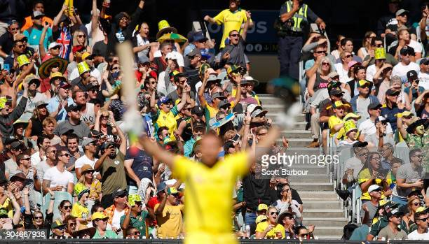 The crowd cheers as Aaron Finch of Australia celebrates reaching his century during game one of the One Day International Series between Australia...