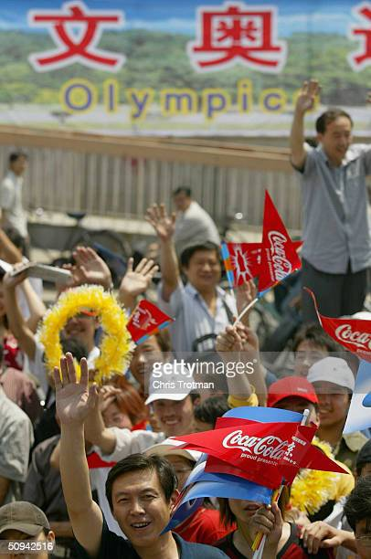 The crowd cheers on the flame as it passes during the ATHENS 2004 Olympic Torch Relay on June 9 2004 in Beijing China The Olympic Flame travels to 34...