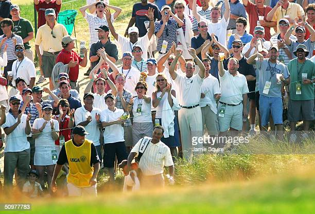 The crowd cheers Tiger Woods as he carries his bag up the fairway alongside his caddie Steve Williams after Woods made an eagle on the 18th hole...