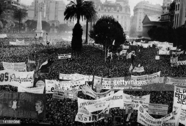 The crowd displaying various banners and the portraits of Evita and Juan Domingo Peron during the Labor Day Buenos Aires 1940s