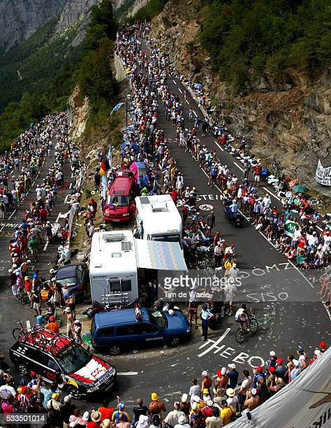 The crowd eagerly await the riders as Ivan Basso cycles past during the stage 16 mountain time trial of the 2004 Tour de France from Bourg d'Oisans...