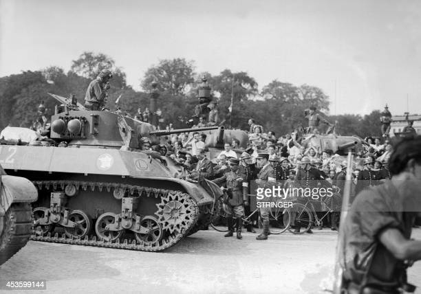 The crowd flanked by firemen greets a tank of the Leclerc Division during the military parade on August 26 Place de la Concorde the day after the...