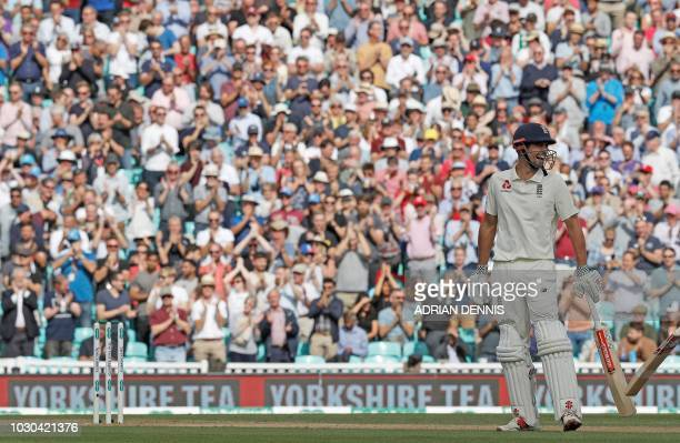 The crowd gives a standing ovation as England's Alastair Cook reacts after playing a shot to become the fifthhighest run scorer in Test history...