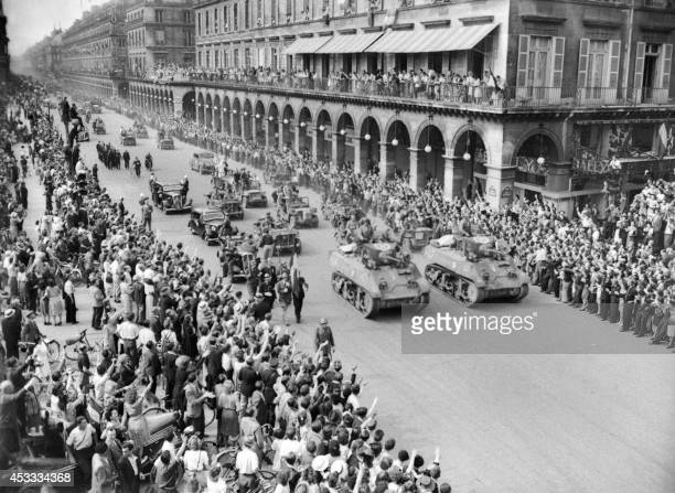 The crowd greets members of the French Forces of the Interior and tanks of the Leclerc Division parading on August 26, 1944 down Rivoli street, the...