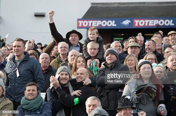 The crowd in grandstand and paddock cheer the horses running in first race during the 2016 Coral Welsh Grand National at Chepstow Racecourse on...