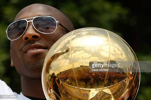 The crowd is reflected in the championship trophy held by Los Angeles Lakers guard Kobe Bryant as he rides in the victory parade for the the NBA...