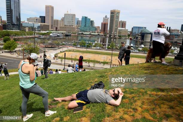 The crowd lingers on a hill after watching the Thunderbirds and Blue Angels preform a flyover on May 02, 2020 in Baltimore, Maryland. The Blue Angels...