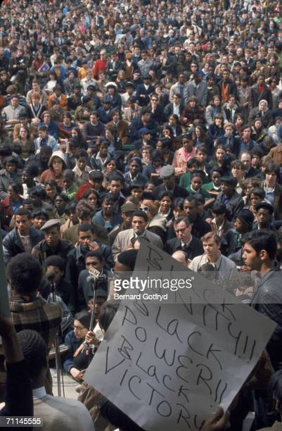 The crowd listens to a speaker as another person on stage holds a sign at an antiwar demonstration at the bandshell in Central Park New York April 27...