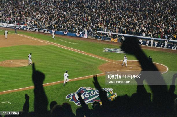 The crowd of spectators celebrate asTino Martinez of the New York Yankees sends a grand slam home run into the upper deck during Game One of the...
