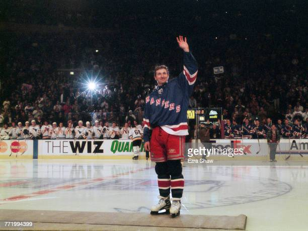 The crowd of spectators, players and team mates applaud as Wayne Gretzky of the New York Rangers waves in salute on his retirement after the National...