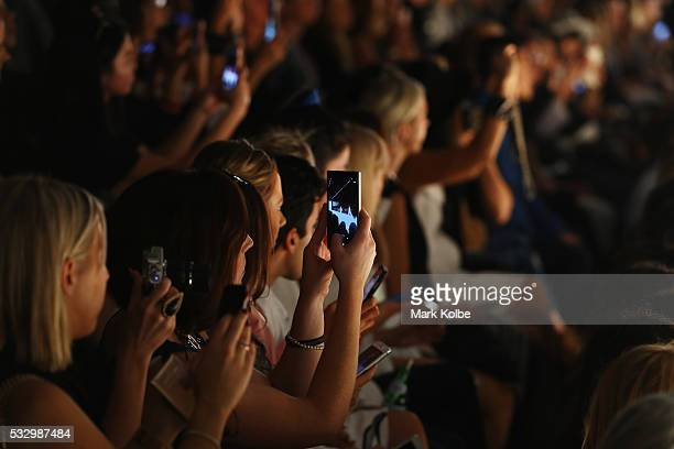 The crowd photograph the show on thier mobile phones as a model walks the runway during The Innovators Fashion Design Studio show during MercedesBenz...