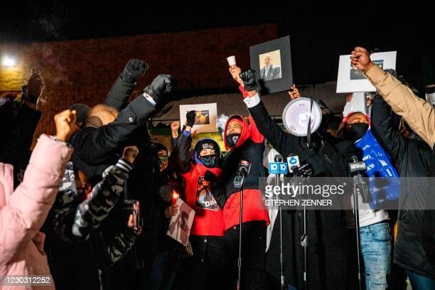 The crowd raises their fists around Hill's daughter Karissa Hill, and nephew Terry Fagain at a press conference and candlelight vigil for Andre Hill...