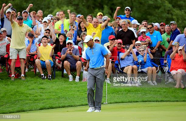 The crowd reacts with Tiger Woods as he makes a birdie putt on the 12th green during the Second Round of the World Golf Championships-Bridgestone...