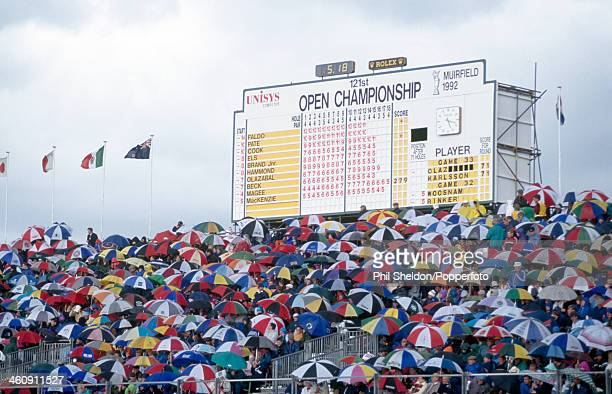 The crowd sheltering from the rain in front of the scoreboard during the British Open Golf Championship held at the Muirfield Golf Links Scotland...