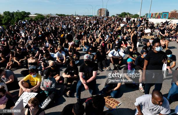 The crowd sits during a march to protest the death of George Floyd on the I35W bridge over the Mississippi River on May 31 2020 in Minneapolis...