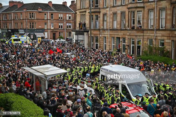 The crowd waits for police to escort two men detained by the Home Office after protestors blocked the immigration van from leaving Kenmure Street on...
