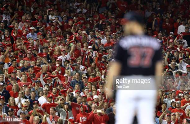 The crowd watch as Stephen Strasburg of the Washington Nationals prepares to pitch in the seventh inning of the game three of the National League...