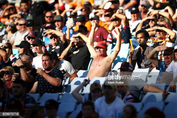 The crowd watch on during the round one NRL match between the Wests Tigers and the Sydney Roosters at ANZ Stadium on March 10 2018 in Sydney Australia