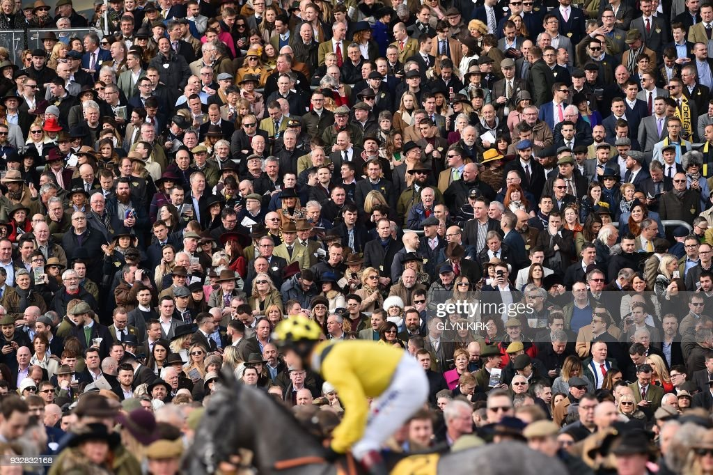 TOPSHOT - The crowd watch the horses going to post for the first race on the final day of the Cheltenham Festival horse racing meet at Cheltenham Racecourse in Gloucestershire, south-west England, on March 16, 2018. KIRK