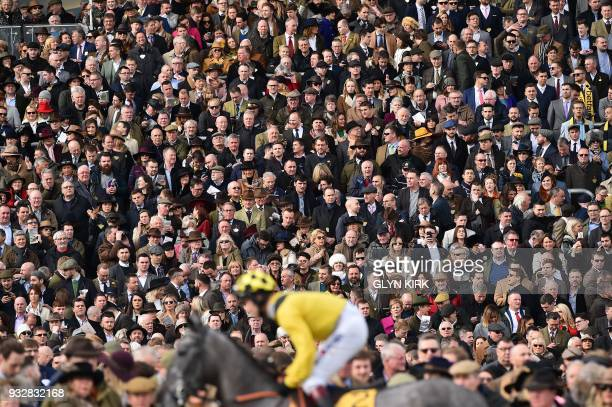 The crowd watch the horses going to post for the first race on the final day of the Cheltenham Festival horse racing meet at Cheltenham Racecourse in...